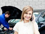 Man repairing car of phoning woman