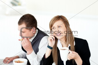 Charming businesswoman drinking coffee while her husband eating