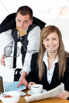 Charming businesswoman reading the newspaper while her husband e