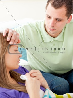 Assertive man feeling temperature of his ill girlfriend holding tissue lying on a sofa