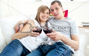 Beautiful young couple lying on the sofa drinking wine