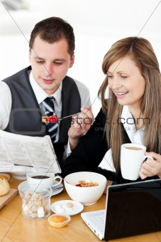 Positive couple of businesspeople having breakfast reading the n