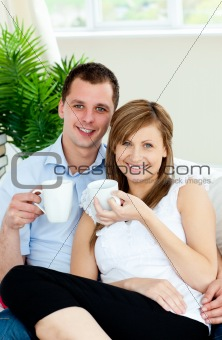 Charming couple holding cups of coffee smiling at the camera
