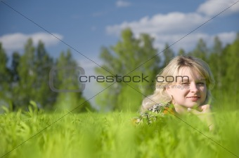 Beautiful young woman lying on the nature