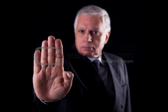 old businessman  with his hand raised in signal to stop