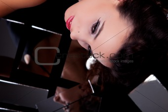 Beautiful woman viewed from above, looking sideways, with mirrors underneath