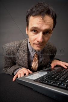 Amusing portrait of man on workplace at dark office