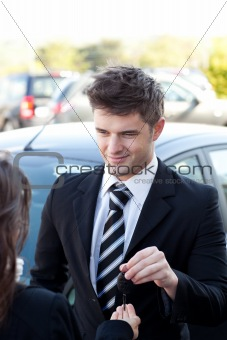 Charming salesman giving a customer car keys