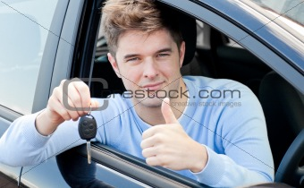 Positive young man holding a key sitting in a car