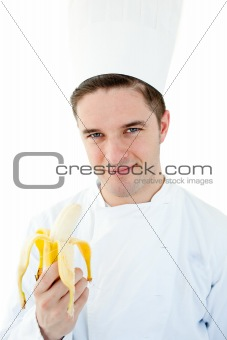 Charming male cook holding banana smiling at the camera