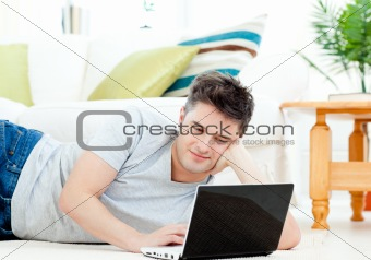 Positive young man using his laptop lying on the floor