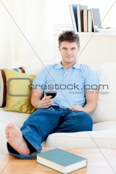 Charming man holding a wineglass sitting on the sofa