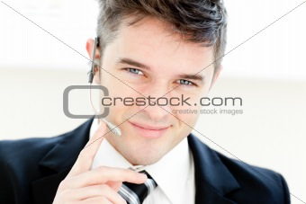 Charming young businessman with headphones smiling at the camera