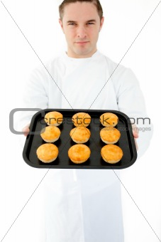Positive male cook holding muffin