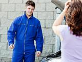 Handsome mechanic at the garage with a desperate woman