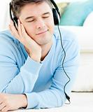 Relaxed young man listen to music with headphones