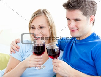 Affectionate couple drinking wine sitting on a sofa