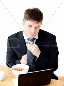 Attractive young businessman making his tie looking at his lapto