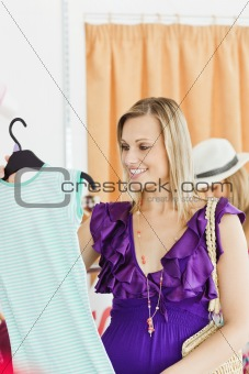 Caucasian blond woman looking at a shirt in a clothes store