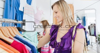 Elegant young woman choosing clothes with her friend
