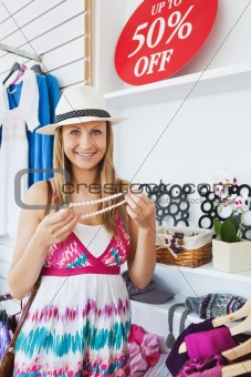 Positive young woman choosing a necklace smiling at the camera