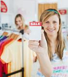 Caucasian blond woman holding a sale paper into the camera