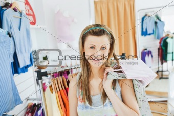 Beautiful blond woman holding shopping bags smiling at the camer