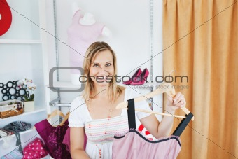 Positive  woman holding a dress smiling at the camera