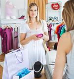 Serious young woman buying clotheslooking at the camera