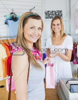 Delighted woman taking shopping bag of a saleswoman