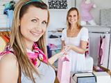 Pretty woman taking shopping bag smilig at the camera