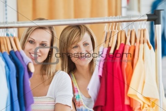 Beautiful female friends doing shopping choosing shirts