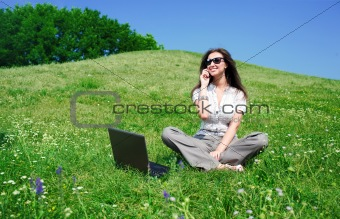 Beautiful woman with notebook and mobile phone sit on hill
