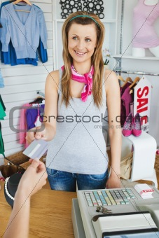Portrait of a charismatic saleswoman giving a customer a card