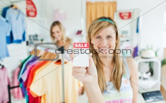 Radiant young woman holding a sale paper into the camera