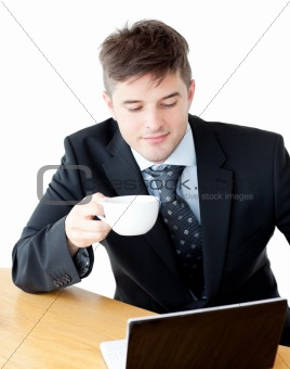 Charismatic businesman drinking coffee using his laptop