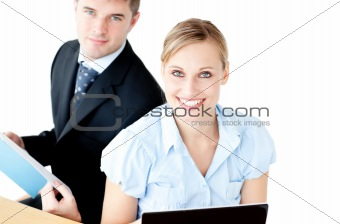 Ambitious couple of businesspeople using a lapop and reading a d