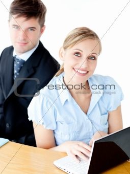 Attractive couple of businesspeople using their laptop at the ta