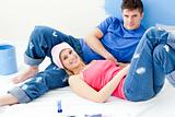 Cute couple relaxing after paiting a room