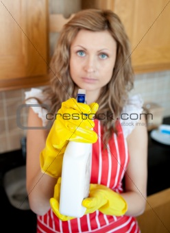 Beautiful blond woman holding cleansing agent into the camera