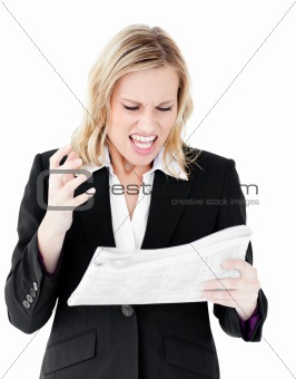 Aggressive businesswoman looking at a newspaper shouting
