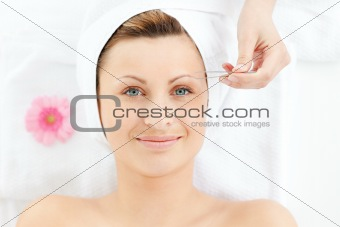 Charming woman using tweezers