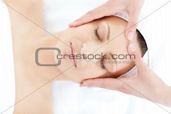 Caucasian young woman receiving a facial massage