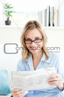 Charming businesswoman reading the newspaper sitting on the sofa at home