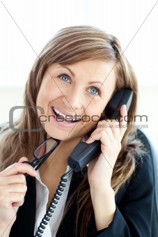 Attractive businesswoman talking on phone holding glasses against white background