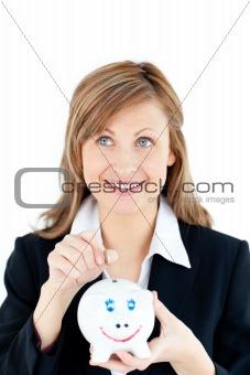 Caucasian woman putting money in a piggybank