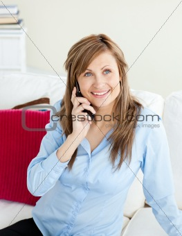 Attractive young businesswoman talking on phone sitting on a sof