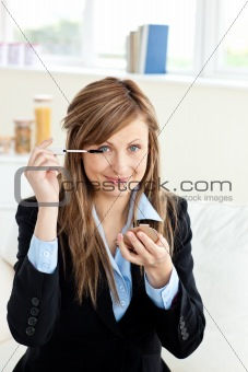 Beautiful businesswoman using mascara looking at the camera