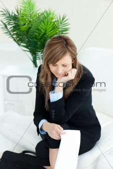 Thoughtful caucasian businesswoman sitting on a sofa holding a p