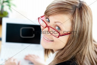 Animated businesswoman using her laptop looking at the camera